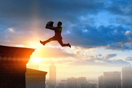 Jumping over precipice, challenge concept. Standard-Bild - 128812653