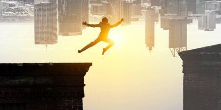 Jumping over precipice, challenge concept. Standard-Bild - 128812674