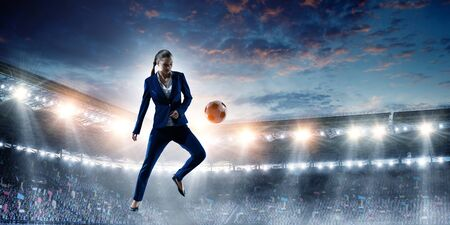 Business woman playing footbal on stadium Stock Photo