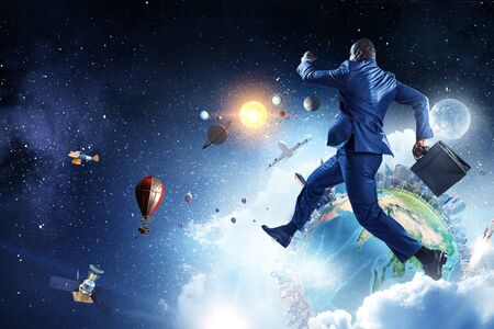 Black businessman running near Earth planet with city skyline on sky and space background