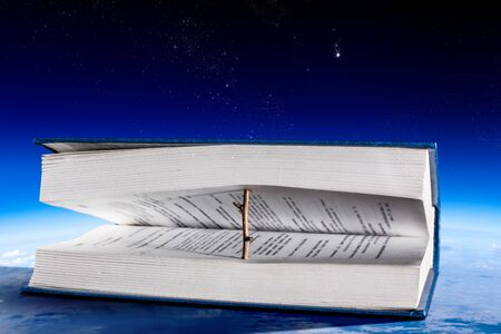 Book open with wooden natural bookmark on blue sky background