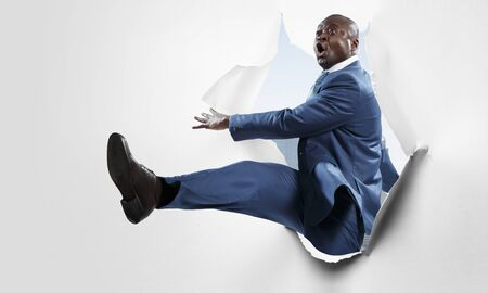 Breakthrough paper hole with a black businessman Standard-Bild