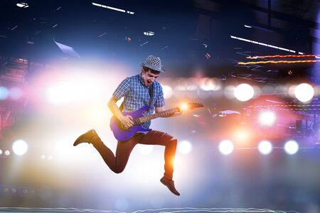 Guitar player jumping with guitar while playing
