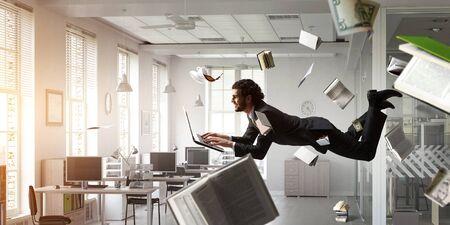 Man flies and works on laptop. Mixed media Standard-Bild - 129001526