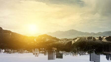 Summer mountain hills landscape with cityscape turned upside down . Mixed media Reklamní fotografie
