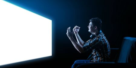 Businessman watching TV . Mixed media Фото со стока