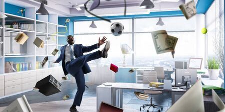 Black businessman playing footbal in office Stock Photo