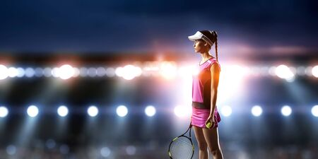Young woman playing tennis on a stadium 스톡 콘텐츠