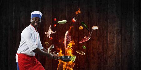 Black chef creative cooking. Mixed media. Stockfoto