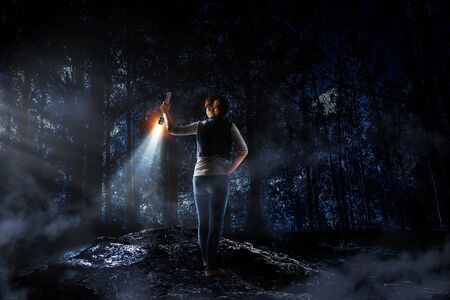 Young woman holding a flashlight Imagens