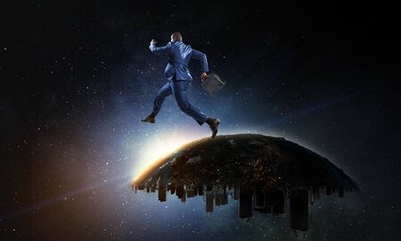 Back view of a black businessman jumping and running from urban Earth planet into starry space Reklamní fotografie - 129257616