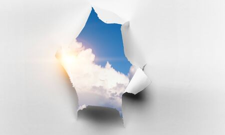 A hole in a sheet of paper with sky view
