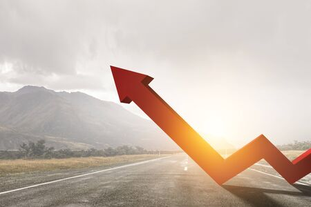 Orange zigzag increasing arrow standing on highway against mountain landscape and cloudy sky background