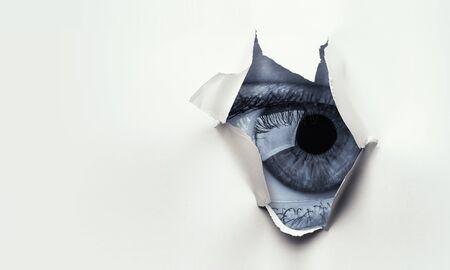 Ojo mirando desde el agujero de la hoja de papel rasgada