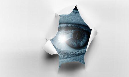 Eye watching from the hole of torn paper sheet Foto de archivo