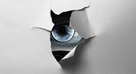 Eye with lunar iris watching from the hole of torn paper sheet