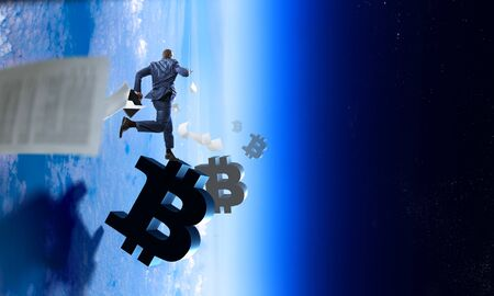 Back view of businessman in a blue suit with briefcase, running on bitcoin marks with falling down papers, atmosphere space background