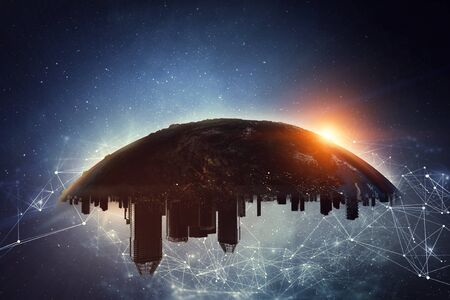 Earth with city skyline turned upside down, sun and stars Stock Photo