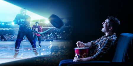 Young man watching ice hockey game on TV