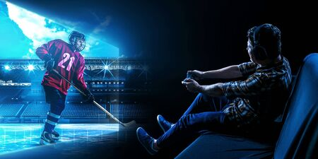 Man sitting on sofa and playing hockey game with joystick. Mixed media Фото со стока