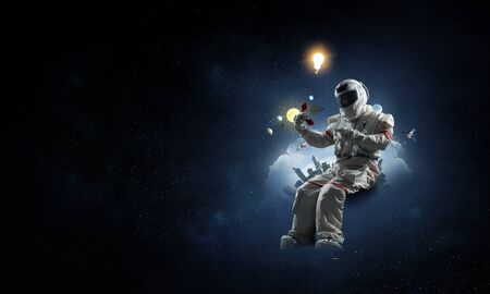 Astronaut in a space-suit sitting on a playful globe on starry sky background 写真素材