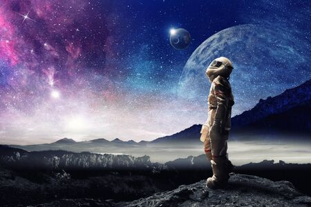 Astronaut in a space-suit looking at planets in the sky
