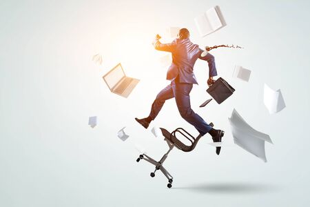 back view of running black businessman with briefcase and falling around office objects