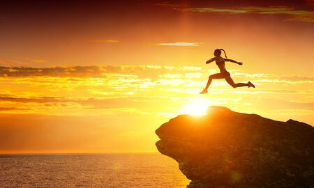 Woman jumping over mountain precipice in front of sunset Imagens