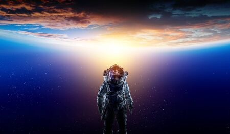 Astronaut in a space-suit in outer space beside a planet