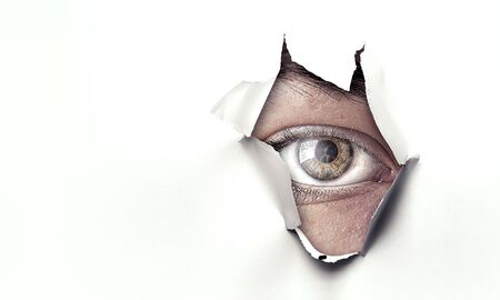 Male eye looks through hole in paper background. Mixed media