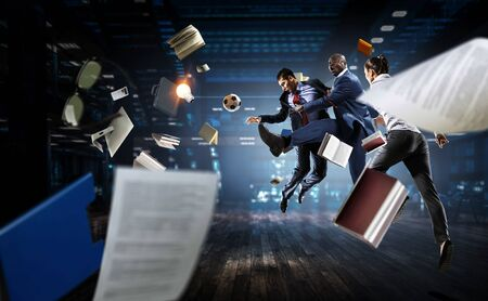 Afroamerican businessman in office kicking ball. Mixed media