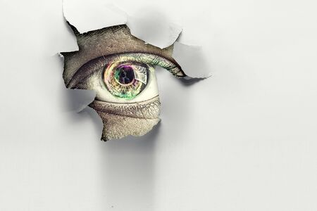 Eye peeping through hole. Mixed media Banco de Imagens - 132815396