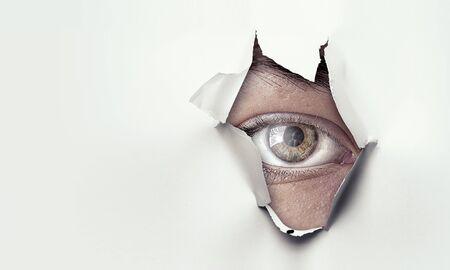 Eye peeping through hole. Mixed media