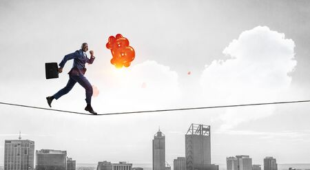 Businessman running on rope. Mixed media Reklamní fotografie