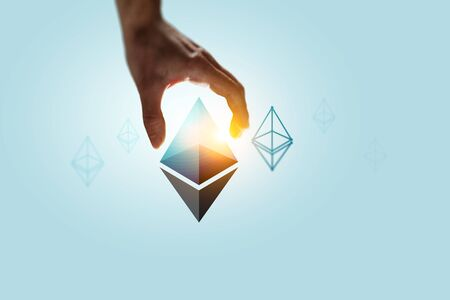 Male hand on blue background take ethereum symbol. 3d rendering Stock Photo - 132680851
