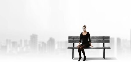 Woman mime in black suit sitting on bench. Mixed media Stock Photo