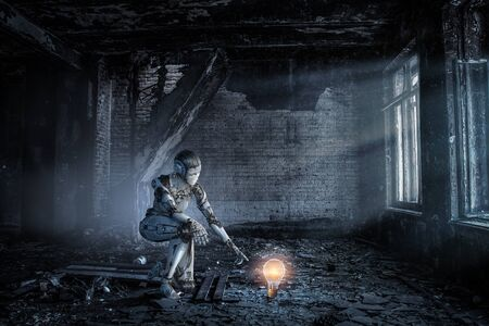 Cyborg woman benting knee to touch glowing bulb. Mixed media 写真素材