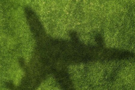 Top view of airplane shadow on green grass 写真素材