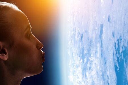 Girl kissing Earth planet . Mixed media 写真素材