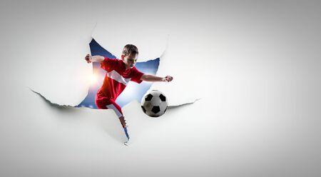 Kid footballer breaking through white paper. Mixed media