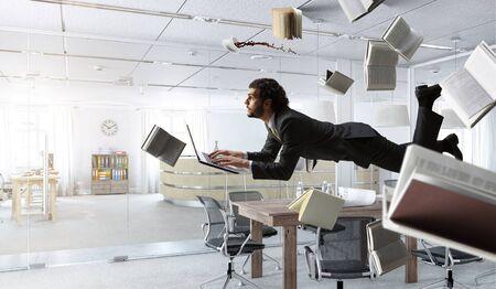Man flies and works on laptop. Mixed media 版權商用圖片 - 135452451