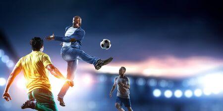 Afroamerican man in casual at stadium kicking ball. Mixed media