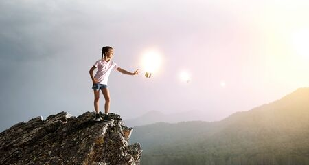 Kid girl of school age glass glowing bulb. Mixed media Reklamní fotografie