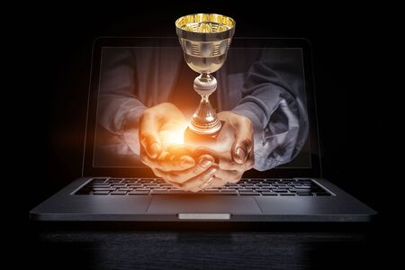 Close of male hands showing golden cup out of laptop screen. Mixed media 写真素材