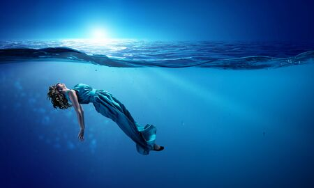 Young beautiful woman in green dress underwater