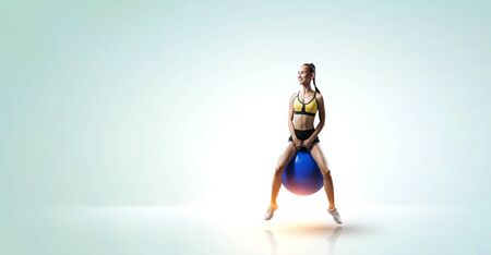 Pretty young fitness woman jumping on fitball. Mixed media