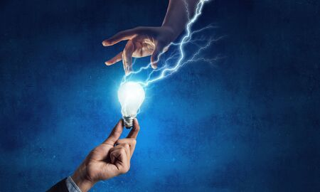 Business hand holding glowing light bulb with lightning