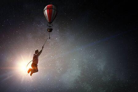 Child fly on aerostat. Mixed media 写真素材