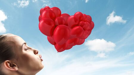 Profile of girl giving a kiss and red balloons 写真素材