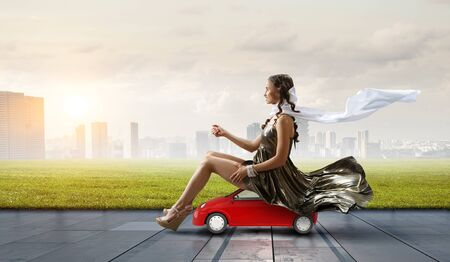 Businesswoman have childhood dream sitting on toy car with city background. Mixed media Imagens